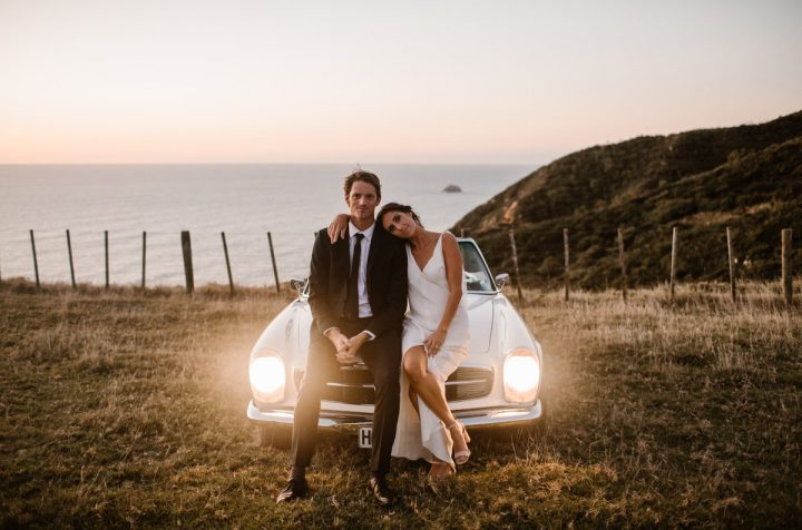 Frank and Peggy Photography Wild Hearts Wedding Vendor Directory - unobtrusive friendly photographer and lover of golden light and beautiful soft hues after sunset, capturing happiness and all that surrounds it - bride and groom in front of vintage car with lights on